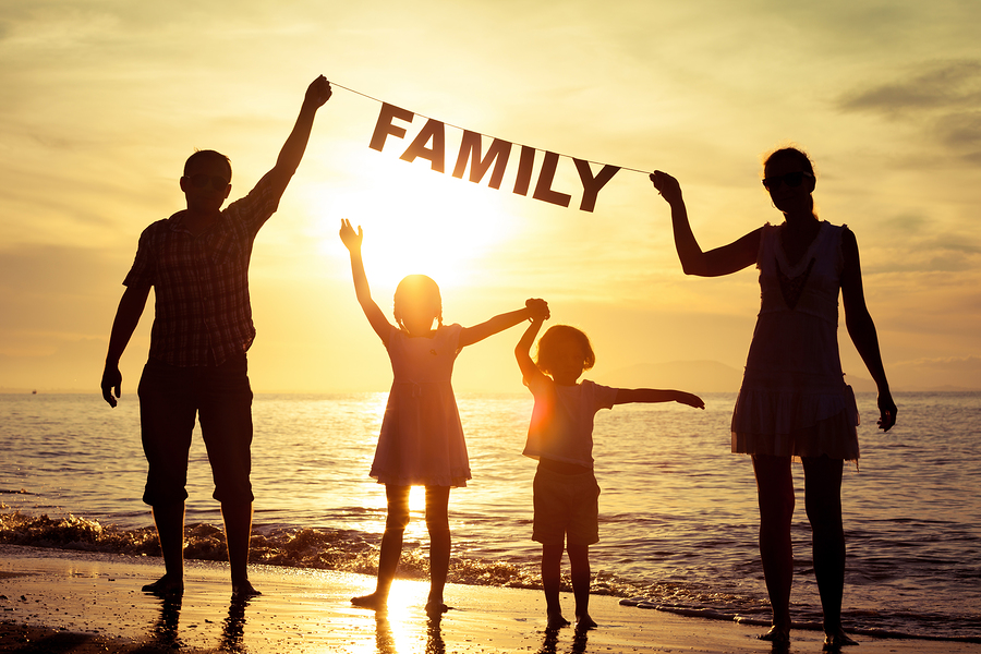 "Happy family standing on the beach at the sunset time. Parents hold in the hands inscription ""Family"". Concept of happy family."