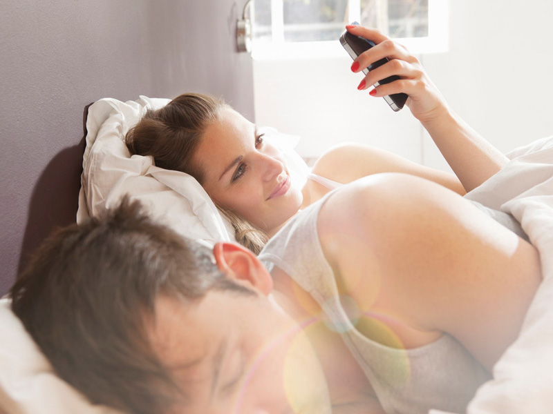 Woman checking mobilephone, man asleep in bedroom.