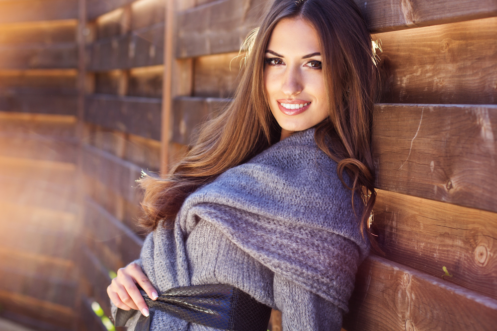 Young fashion smiling girl wearing warm knitted clothes near wooden wall